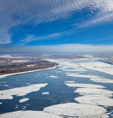 Floating ice floes are drifting on the great river — Stok fotoğraf