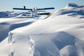 Biplane parked on snow drifts — Stock Photo