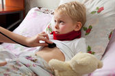 Sick boy lies in bed — Stock Photo