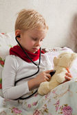 Sick boy is playing with a stethoscope — Stock Photo