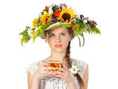 Beautiful girl in hat of flowers and cup of tea — Stock Photo