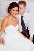 Bride and groom are sitting on the bed in the hotel — Stock Photo