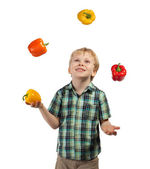 Little boy juggles some fruits and vegetables — Stock Photo