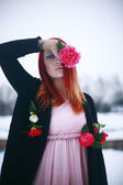 Red-haired girl in the winter garden with roses — Foto de Stock