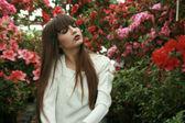 Brunette woman  in azalea garden. — Stock Photo