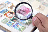 Hand with magnifying glass and stamp album — Stock Photo