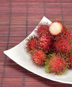 Tropical fruits rambutan with plate on bamboo mat — Stock Photo