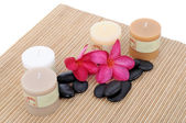 Beautiful frangipani flowers with candles and spa stone isolated on white background — Stock Photo