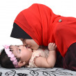 Young Asian muslim mother kissing her cute baby girl isolated on white background — Stock Photo #37807001
