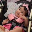 Cute Asian baby girl smiling while sitting in her stroller — Stock Photo #44934863