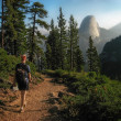 Stock Photo: Hiker Walking on Trail with Half Dome in Background