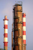 Oil refinery chimneys and tower — Stok fotoğraf