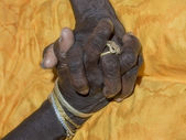 Hands of an old lady joined on her yellow dress — Stock Photo