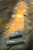 Old rusty saw on the wooden background — Stock fotografie