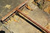 Steel rake on the cement floor. — Stock Photo