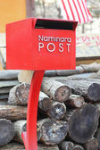 Red postbox with a pile of wood. — Zdjęcie stockowe