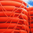 Stock Photo: Stacked orange rescue round buoy, semarine lifesaver