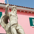 图库照片: Cupids Statue - with pink buildings.