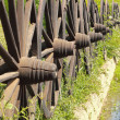 Old wagon wheels arranged in a fence. — Stock Photo