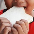 Child eating a delicious slice of bread — Stock Photo #39667811