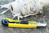 The yellow stationery knife on a white rope. — Stock Photo