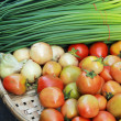 Fresh tomatoes with onion flowers on the market. — Stock Photo #40264003