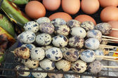 Chicken and quail eggs on the grill. — Stock Photo