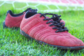 Red shoes on green grass with goal football — Stockfoto