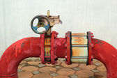 Red rusty metal industrial water pipes with a valve. — Stock Photo
