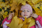 Girl covered by autumn leaves — Stock Photo