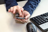 Mobile in hands, mouse and keyboard — Stock Photo