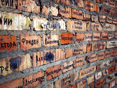 Brick wall with cyrillic names — Stock Photo