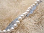 White pearl and blue lace on straw — Stock Photo