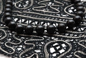 Black pearl necklace on black lace — Stock Photo