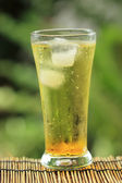 Gold guarana soft drink with ice cubes — Stock Photo