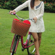 Asian young woman with bicycle — Stock Photo