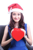 Asian woman with a christmas hat and carrying a chocolate box — Foto Stock