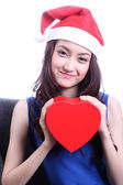 Asian woman with a christmas hat and carrying a chocolate box — Stok fotoğraf