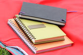 Three notepads over red mat  — Stock Photo