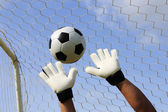 Goalkeeper's hands and foot ball — Stock Photo