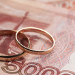 Stock Photo: Wedding rings on money