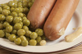 Sausages with green peas and mustard — Stock Photo