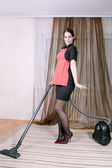 Attractive housewife with vacuum cleaner — Stok fotoğraf