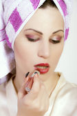 Beautiful woman applying lipstick — Stock Photo