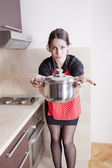 Beautiful housewife holding a pan — Stock Photo
