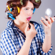 Woman with curlers applying make up — Stock Photo