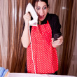 Funny expression of housewife with cell phone and iron — Stock Photo