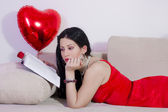 Valentine day. Girl on sofa reading book — Stock Photo
