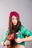 Young woman holding a power tool — Stok fotoğraf