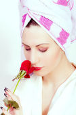 Beautiful young woman with a flower and towel on her head — Stock Photo